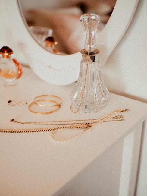 Een witte ladekast met gouden sieraden en een transparante glazen karaf