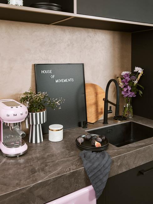 Donkere keukeblad met zwarte kraan met oud roze smeg koffiemachine