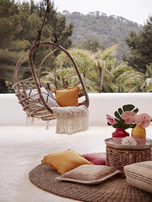Hangende fauteuil met kussens op het terras en rotan bijzettafel