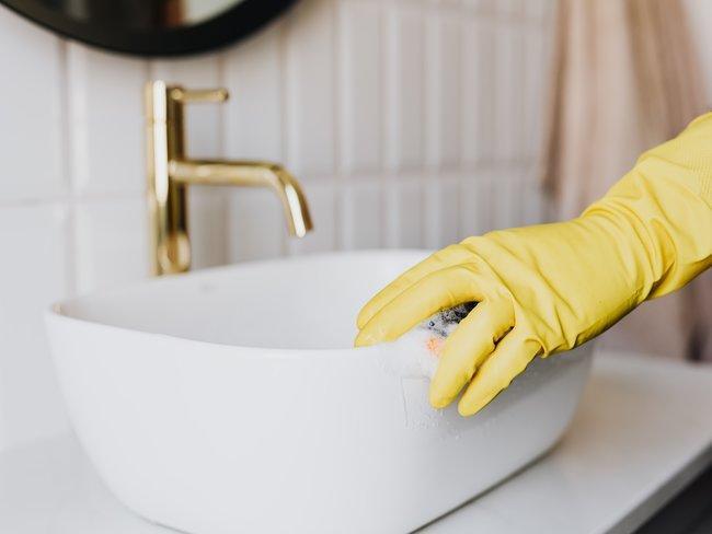 wastafel in badkaer wordt gewassen door hand in gele handschoen met spons kalk verwijderen