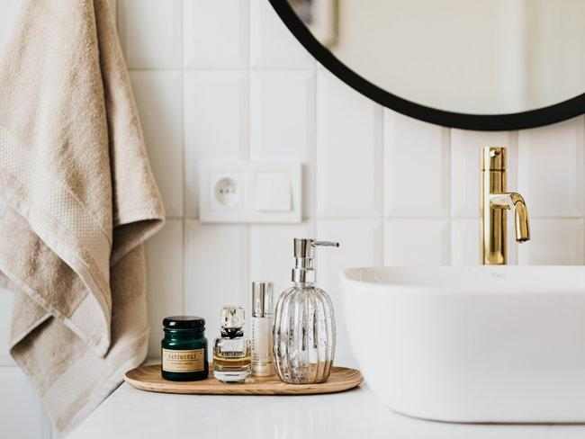 lavabo in badkamer met spiegel, handdoek en schoonheidsartikelen op dienblad