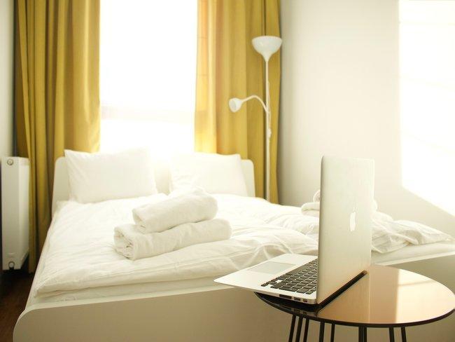 witte slaapkamer met mosterdgele gordij nen en laptop