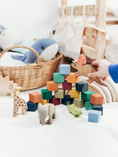 Houten speelgoed in een kinderkamer op een wit vloerkleed