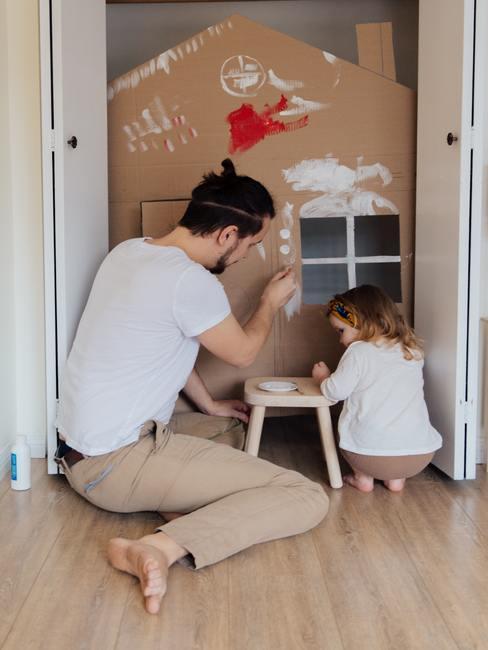 Vader en dochter schilderen een handgemaakt kartonnen huis