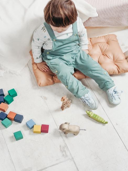 Babykamer groen: de jongen speelt met speelgoed op houten vloer met zachte zitkussen