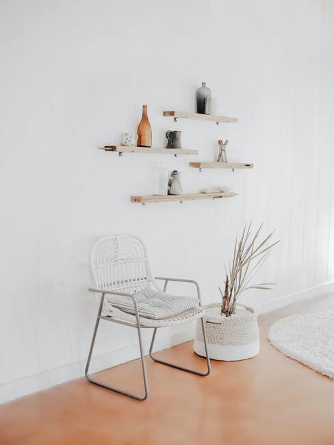Witte stoel naast een pot met plant en witte planken op witte muur