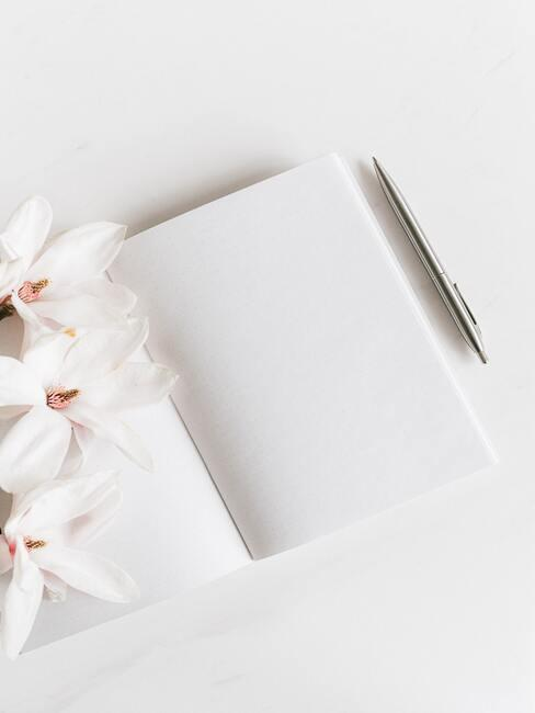Notitieboekje met effen witte pagina's naast een vulpen en bloemen