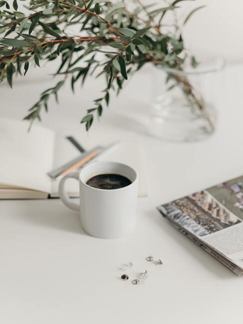 Witte kop met zwarte koffie op een witte tafel met een transparante vaas met bloemen