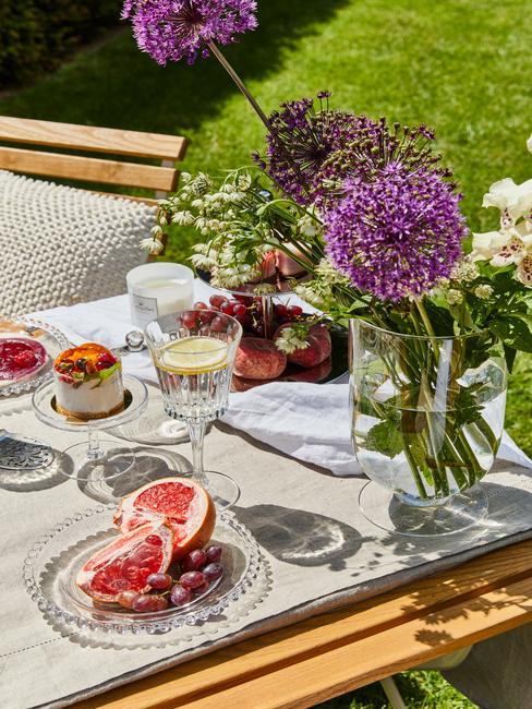 Letnia dekoracja stołu w ogrodzie z lnianim obrusem oraz kwiatami w wazonie