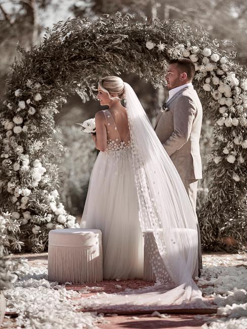 Para młoda stojąca przed łukiem z kwiatów w trakcie ceremoni ślubnej