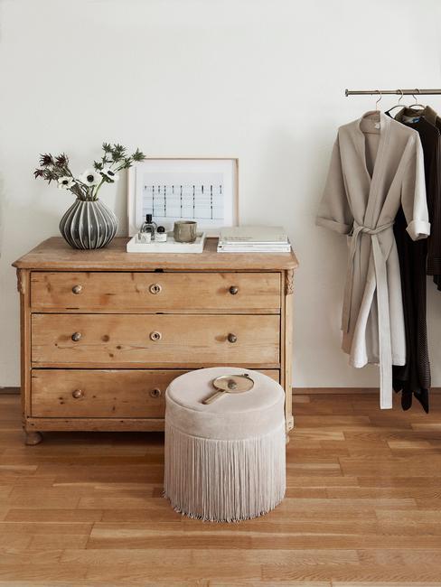 Fragment pomieszczenia z drewnianą komodą, aksamitnym pufem i wieszakime na ubrania