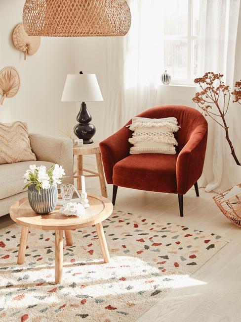 Beżowym salon w stylu boho z sofą, drewnianym stolikiem kawowym i fotelem w odcieniu Living Coral