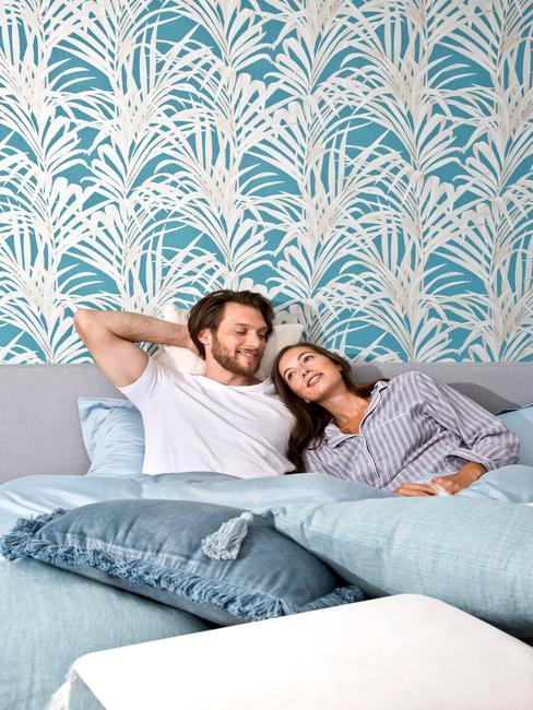 Para leżąca w łóżku w sypialni urządzonej w odcieniach niebieskiego