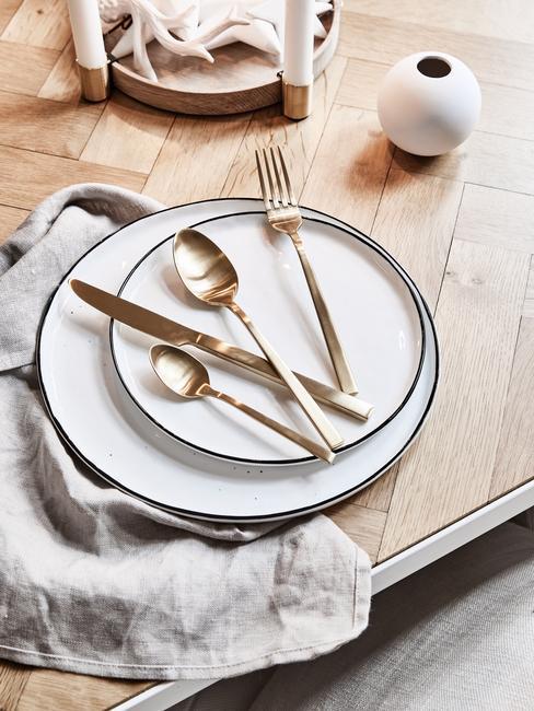 Pozłacana zastawa leżoąca na białym talerzu na drewnianym stole