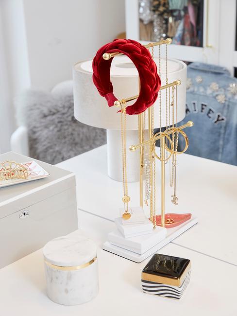 Biały stojak na biżuterię ze złotą biżuterią i czerwoną opaska