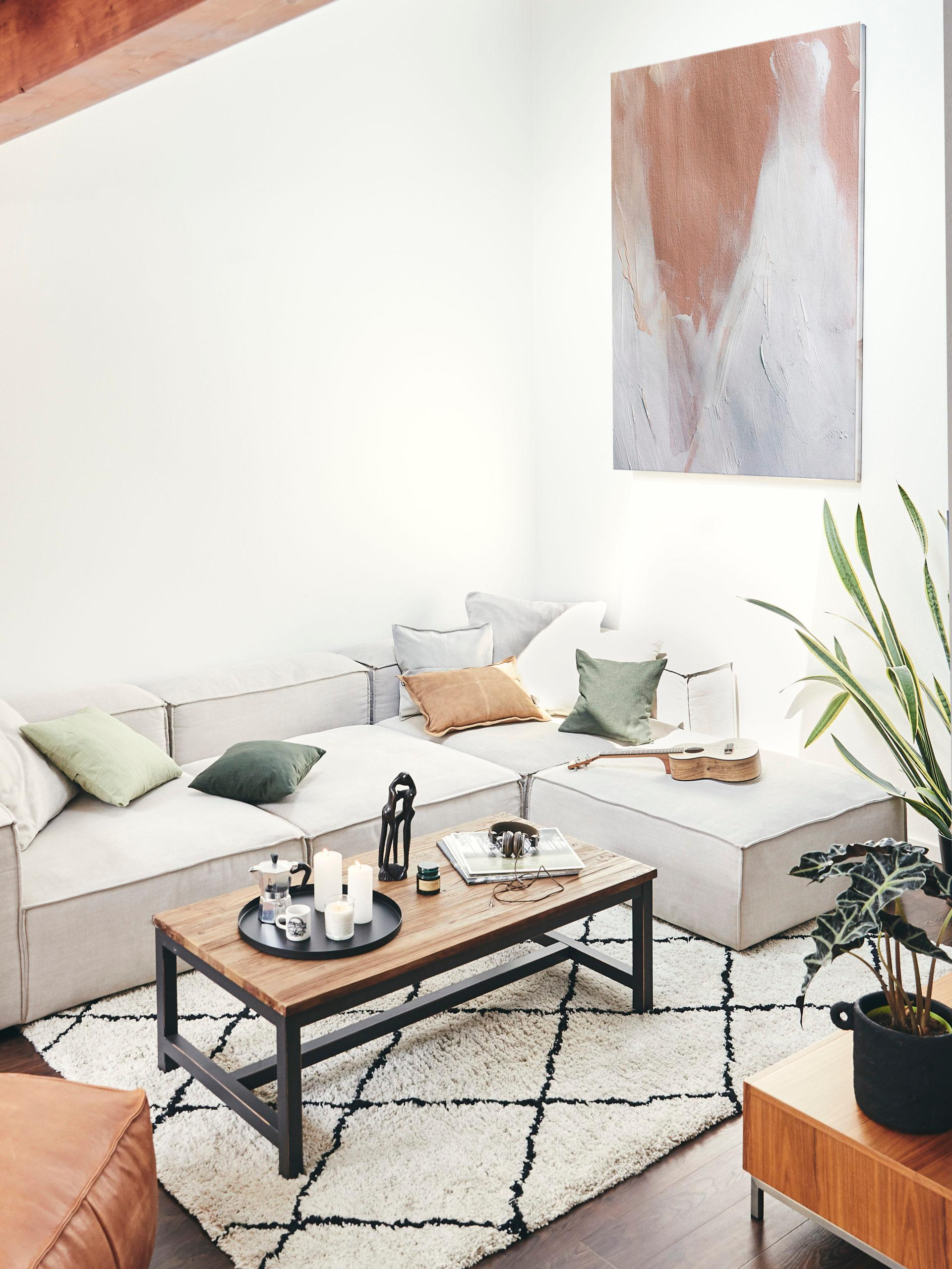 Jasny salon na poddaszu, z beżową narożną kanapą oraz stolikiem kawowym