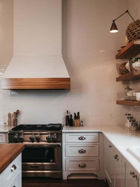 Fragment kuchni z piekarnikiem, okapem, białymi szafkami kuchennymi i regałami