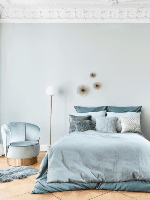 Turkusowa sypialnia z łożkiem, fotelem oraz białą lampą