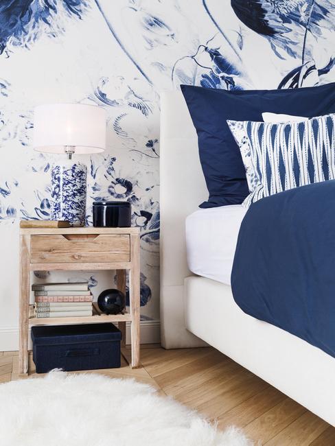 Fragment biało-niebieskiej sypialni z drewnianą szafką oraz lampą