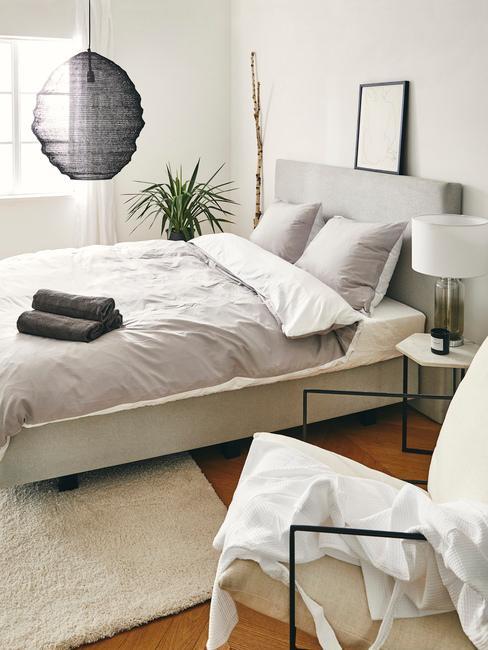 Syialnia z szarymi elementami w postaci poduszek, pościeli i lampy