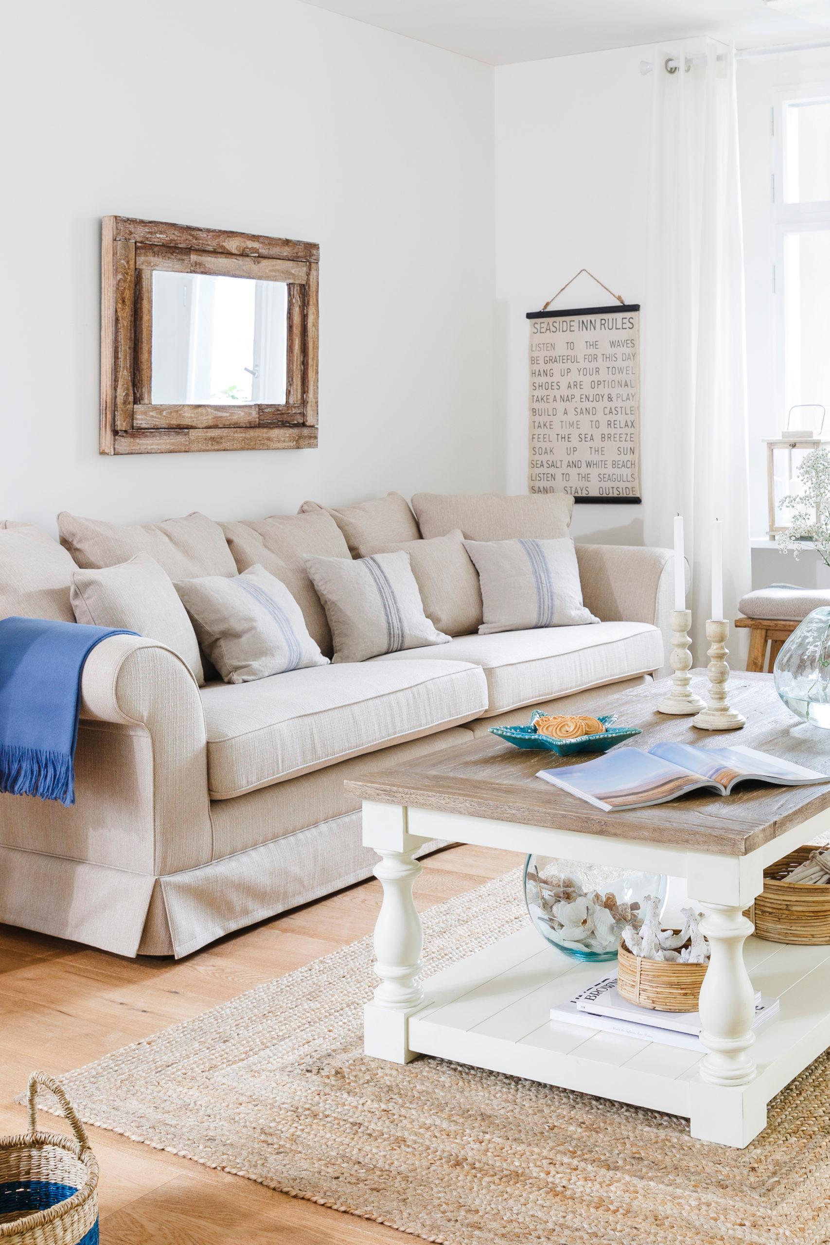 Salon z jasną kanapą z poduszkami, drewnianym stolikiem kawowym i dekoracjami na ścianach