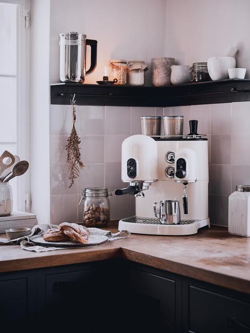Biała kuchnia z drewnianym blatem, czarnymi szafkami oraz ekspresem do kawy
