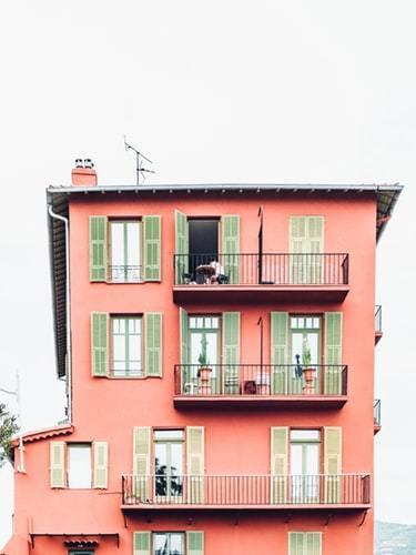 Pomarańczowy budynek z zielonymi okiennicami