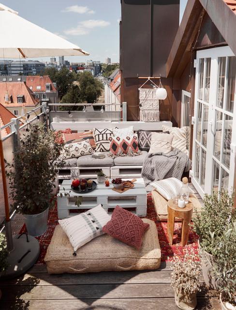 Balkon z kanapą zrobioną z palet, roślina oraz dekoracjami