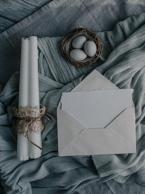 Koperta z kartą, dwie białe świece oraz gniazdko z jajkami