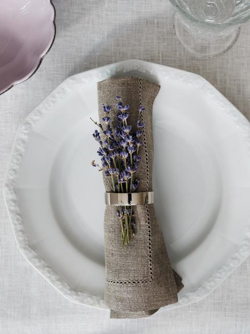 Biała zastawa z lnianą serwetką oraz lawendą