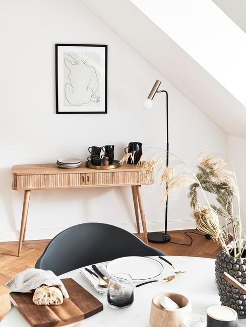 Stolik wykonany z jasnego drewna stojący przy ścianie