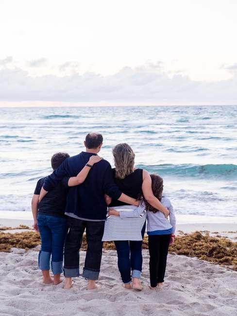 Czteroosobowa rodzica stojąca nad brzegiem morza