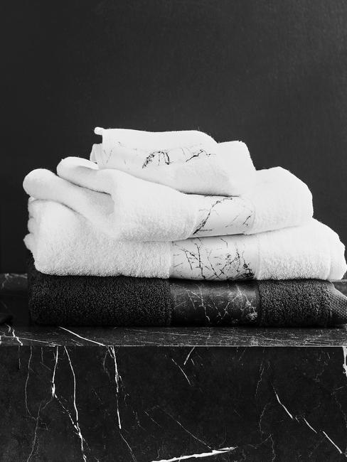 Stolik wykonany z czarnego marmuru na którym ułożone są białe ręczniki