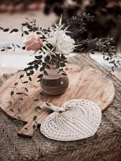 Dekoracje w stylu boho: drewniana deska, wazon z kwiatami oraz wachlarz z juty