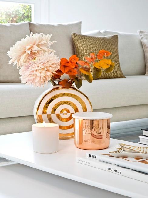 Pomarańczowy wazon z kwiatami na bialym stole w salonie