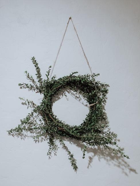 Wiszący wianek na ścianie zrobiony z wiecznie zielonych roślin