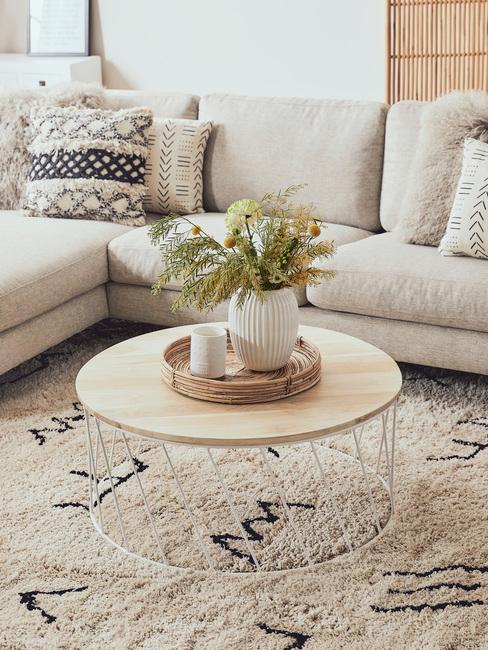 Salon boho za narożną kanapą, dywanem i okrągłym stolikiem kawowym