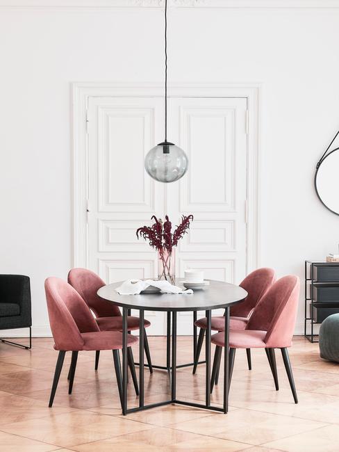 Biała hadalnia z okrągłym, czarnym stołem oraz czterem krzesłami w kolorze brudnego różu