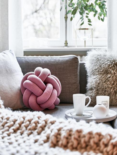 Różowa poduszka supeł leżąca na szarnej kanapie wokół innych poduszek przy kocu z grubego pledu