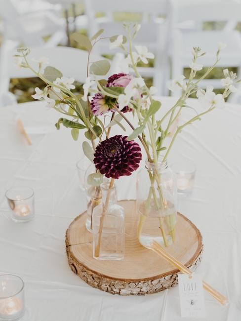 Kwiaty na stół weselny w szklanym wazonie postawione na tacy z pnia drzewa