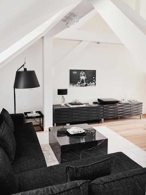 Minimialistyczny salon na poddaszu z czarną kanapą, stolikiem na kawę, komodą i dekoracjami