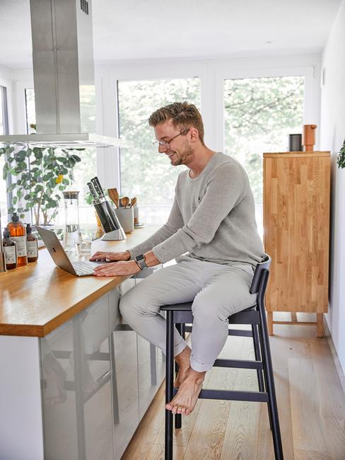 Mężczyna siedzący na czarnym krześle przy blacie kuchennym i pracyjący z domu