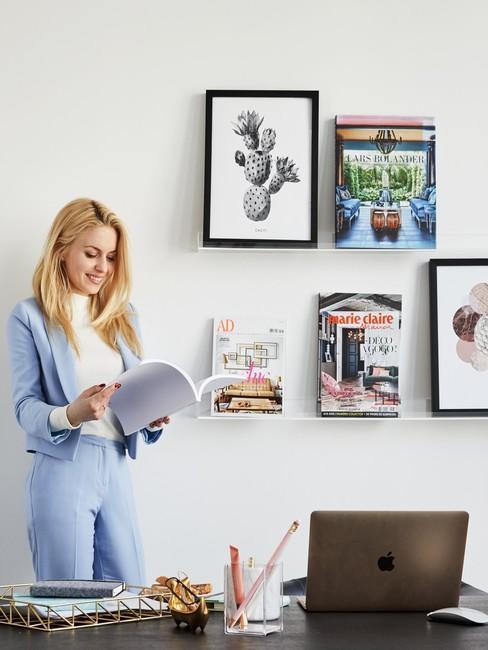 Delia stojąca przy biurku z komputerem przeglądająca gazetę