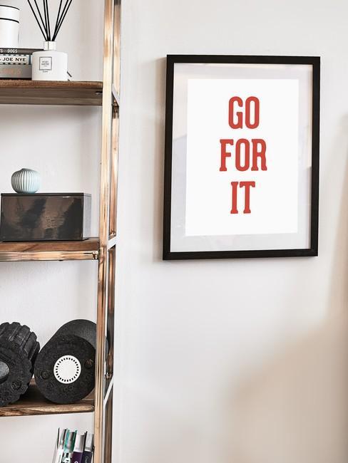 Fragment pokoju na ćwiczeń z półką na sprzęt sportowy oraz plakatem motywacyjnym