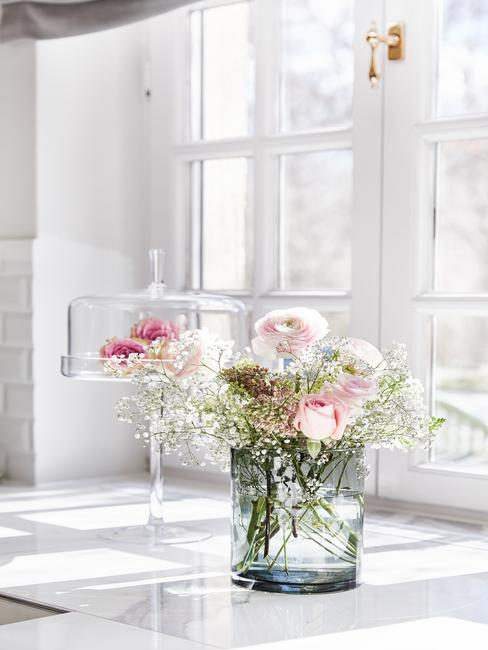 Szklany wazon z bukietem kwiatów obok szklanej patery z ciastem stojące na parapecie w kuchni
