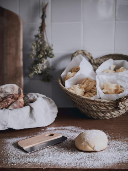Fragment kuchni w stylu rustykalnym z drewnianym blatem oraz białą ścianą z artykułami kuchennymi