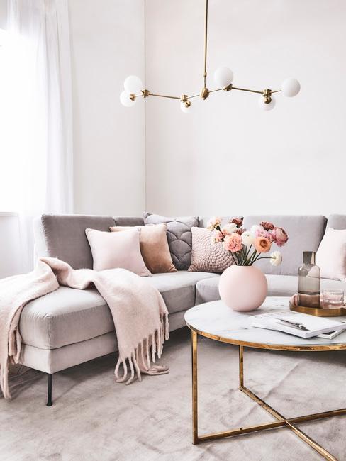 Salon z szarą sofą, zotymi obramówkami mebli oraz tekstyiami w kolorze millennial pink