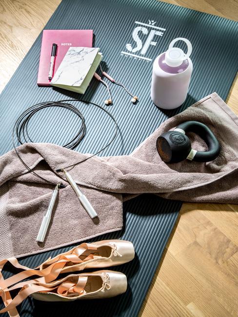 Akcesoria do ćwiczeń: mata, skakanka, hantel oraz butelka na wodę na podłodze w domowej siłowni