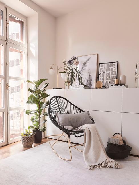 Salon z kremowymi ścianami, białymi szafkami, czarnym fotelem oraz roślinami jako dekoracje