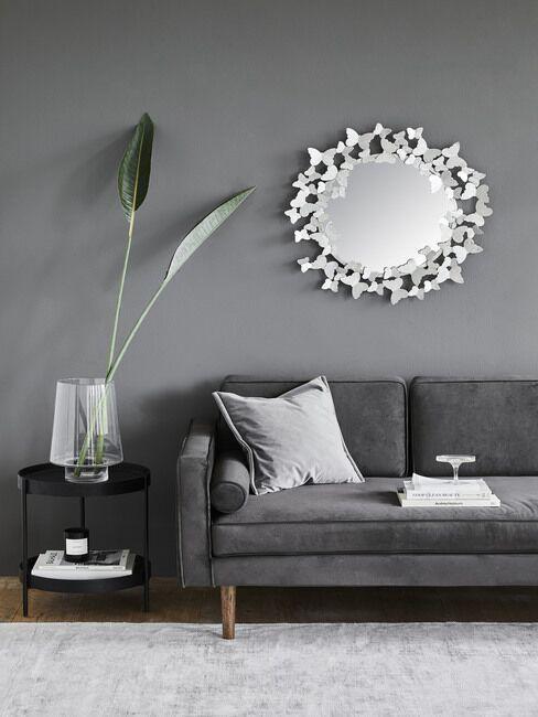 Szara ściana w salonie, na której wisi lustro w srebrnej ramie.
